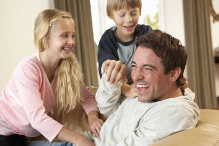 Young father with children having fun on sofa photo