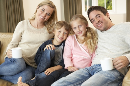 Happy young family sitting on sofa holding cups photo