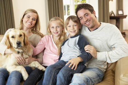 woman couch: Happy young family sitting on sofa holding a dog Stock Photo