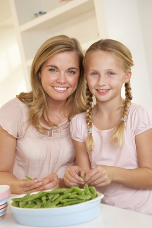 ten year old: Young woman with child splitting pea in kitchen