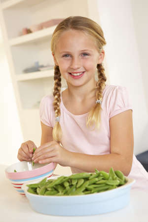 ten year old: Happy girl splitting peas in kitchen