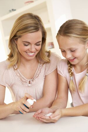 handwash: Mother putting sanitizer on young girls hands Stock Photo