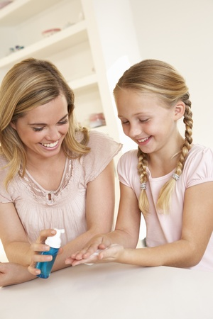 ten year old: Mother putting sanitizer on young girls hands Stock Photo