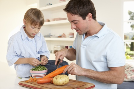 Happy young man with boy peeling vegetables in kitchen photo