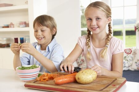 Happy children peeling vegetables in kitchen photo