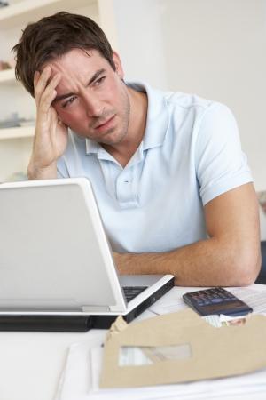 perplesso: Giovane uomo lavorando con computer portatile