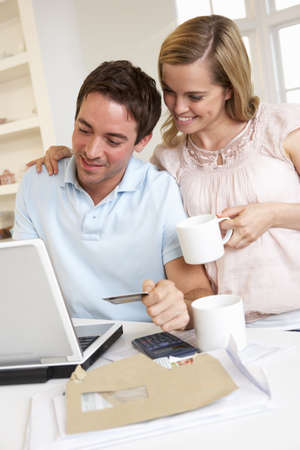 Young couple using credit card on the internet Stock Photo - 9875802