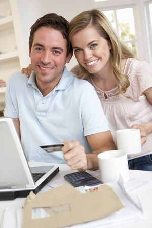 Young couple using credit card on the internet photo
