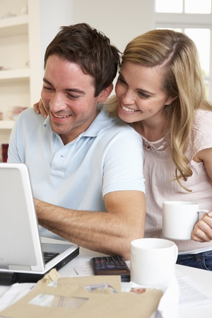 30 years old married couple: Happy young happy couple looking and reading a laptop computer