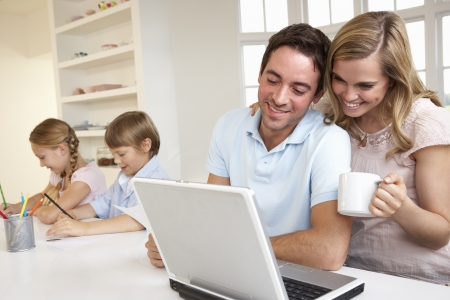 Happy young family looking and reading a laptop computer photo