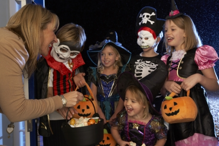 trick or treating: Happy Halloween party with children trick or treating Stock Photo