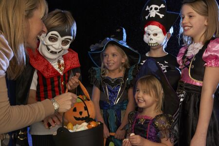 treating: Happy Halloween party with children trick or treating Stock Photo