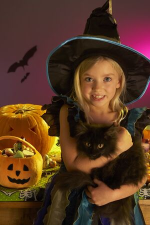 trick or treating: Halloween party with a child holding black cat in hand