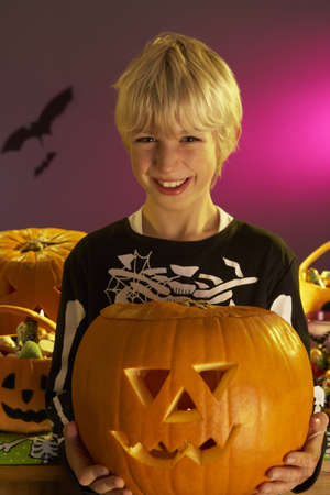 Halloween party with a boy holding carved pumpkin photo