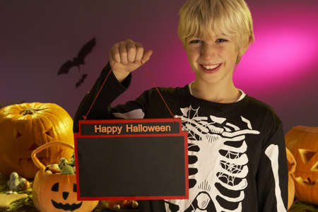Halloween party with a boy child holding sign photo