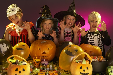 treating: Halloween party with children wearing fancy costumes