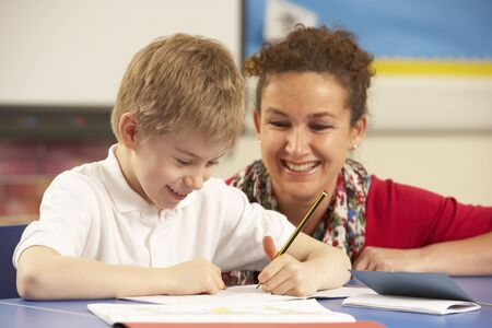 helping children: Schoolboy Studying In Classroom With Teacher Stock Photo