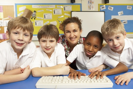 Schoolchildren in IT Class Using Computers with teacher photo