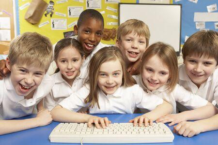 ni�os en la escuela: Escolares en la misma clase utilizando equipos Foto de archivo