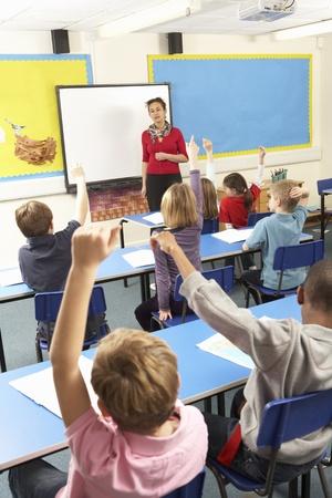 teacher classroom: Schoolchildren Studying In Classroom With Teacher