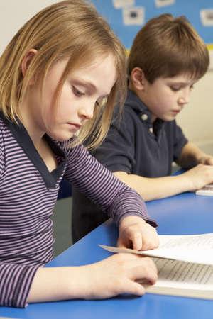 non uniform: Schoolgirl Reading Book In Classroom Stock Photo
