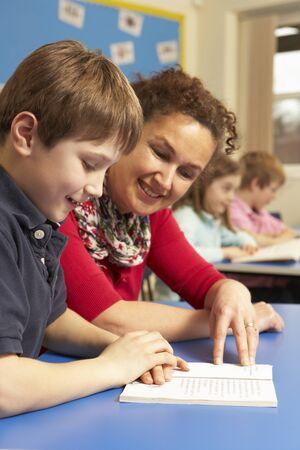 maestra ense�ando: Colegial estudiando en aula con profesor