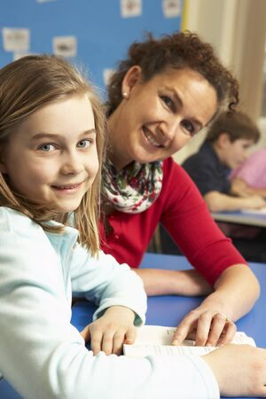 Schoolgirl Studying In Classroom With Teacher photo