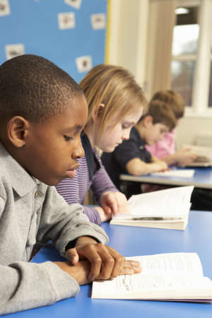 children writing: Schoolboy Reading Book In Classroom