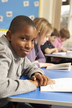 Schoolboy Reading Book In Classroom photo