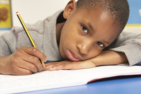 Unhappy Schoolboy Studying In Classroom Stock Photo - 9875962