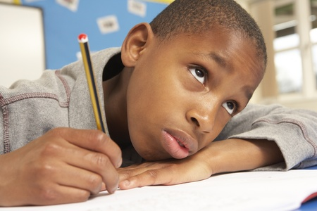 Unhappy Schoolboy Studying In Classroom photo
