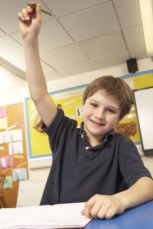 attentive: Schoolboy Answering Question In Classroom