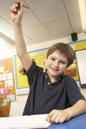 non uniform: Schoolboy Answering Question In Classroom