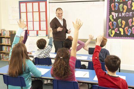 maestra ense�ando: Ni�os en edad escolar estudian en aula con profesor Foto de archivo