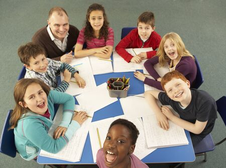 school aged: Overhead View Of Schoolchildren Working Together At Desk With Teacher