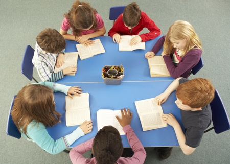 Overhead View Of Schoolchildren Working Together At Desk Zdjęcie Seryjne - 9876179