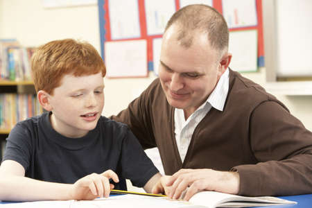 Male Pupil Studying in classroom with teacher photo