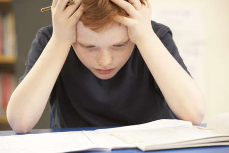 Stressed Schoolboy Studying In Classroom photo