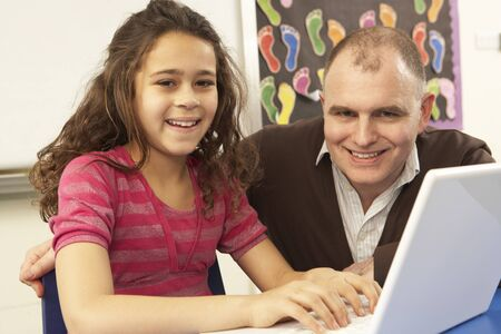 Schoolgirl In IT Class Using Computer With Teacher photo