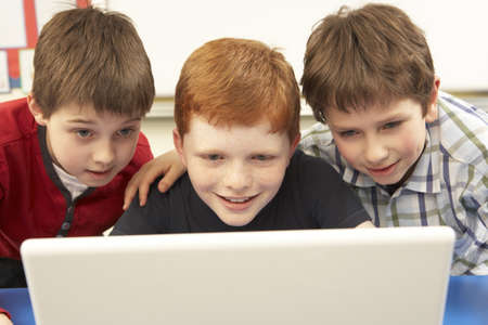 Group Of Schoolboys In IT Class Using Computer photo