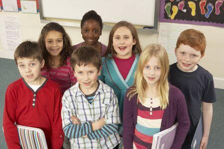 non uniform: Portrait Of Schoolchildren Standing In Classroom
