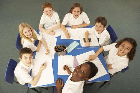 Overhead View Of Schoolchildren Working Together At Desk photo