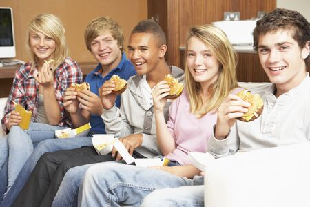 Group Of Teenage Friends Sitting On Sofa At Home Eating Fast Food photo