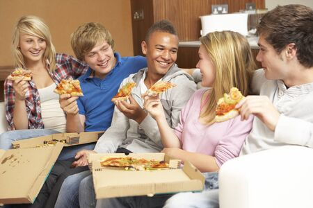 Group Of Teenage Friends Sitting On Sofa At Home Eating Pizza photo