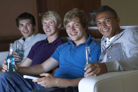 Group Of Teenage Boys Sitting On Sofa At Home Watching Drinking Alcohol Stock Photo - 9876123