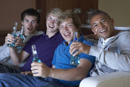Group Of Teenage Boys Sitting On Sofa At Home Watching Drinking Alcohol Stock Photo - 9876077