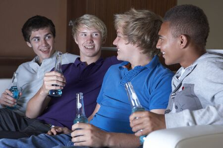 Group Of Teenage Boys Sitting On Sofa At Home Watching Drinking Alcohol photo
