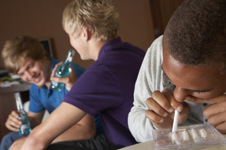 Group Of Teenage Boys Taking Drugs At Home photo