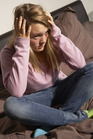 Depressed Teenage Girl Sitting In Bedroom At Home photo