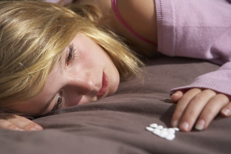addiction alone: Depressed Teenage Girl Sitting In Bedroom With Pills Stock Photo